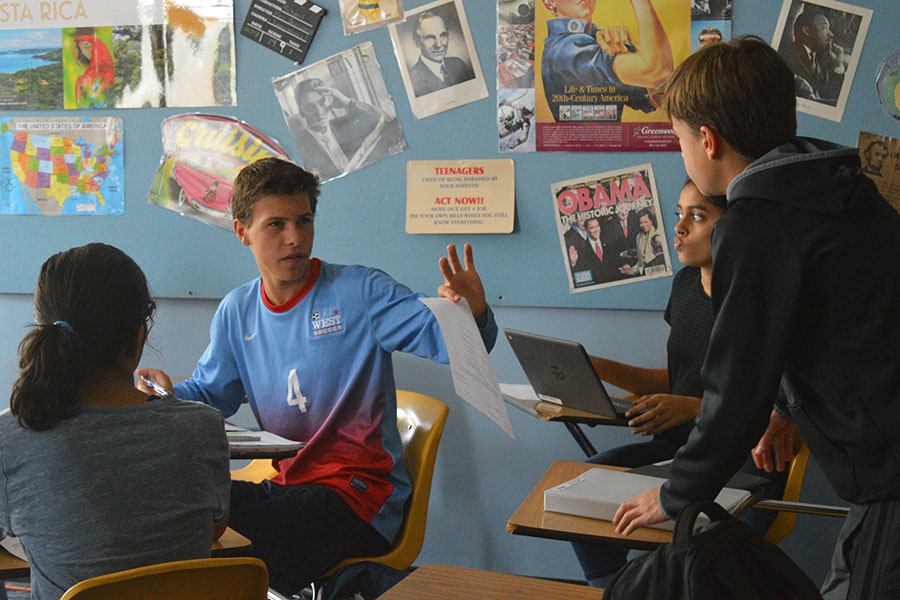 "While working on an assignment in AP Human Geography, freshman Mason Paul discusses his answers. Paul is enrolled in two AP/Honors classes. ""Taking AP/Honors classes are hard because you have a lot of homework, but you get to brag to your friends about taking them,"" Paul said."