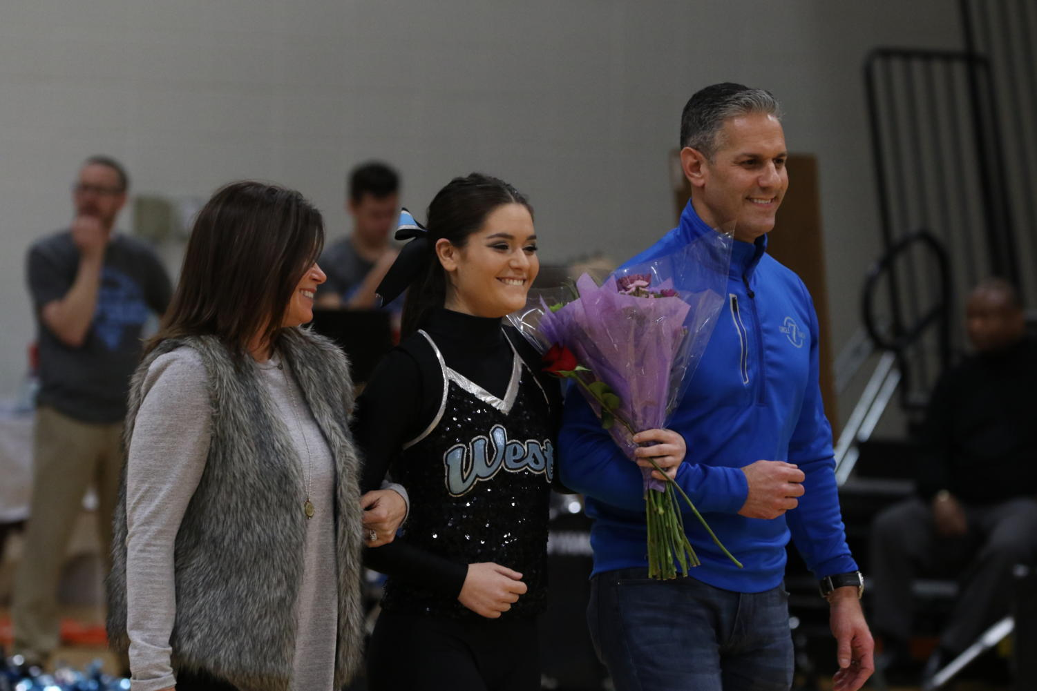 "Walking across the Main Gym on Wednesday, senior Sophia Ferretti is accompanied by her parents, Pete and Tonya Ferretti during the senior Poms ceremony. As the dancers walked, history teacher Zaven  Nalbandian announced the dancers achievements throughout their high school career. ""It was a very bittersweet night,"" Ferretti said. ""I was really happy to have made it this far and I am proud of everything that I have accomplished. I definitely had to fight back my tears when the reality of not being on the team anymore started sinking in."""