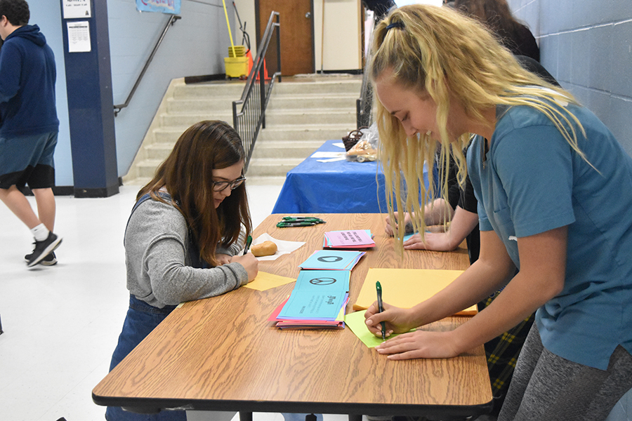 "Stopping on their way into lunch, students write letters for the students of Marjory Stoneman Douglas High School. Students were given the opportunity to write letters the week of Feb. 4-8. ""The goal in doing this is to make the students at Parkland feel love and support as they're approaching the one year anniversary of this difficult time,"" senior Sophie Pellegrino said."