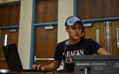 """Sitting at the microphone, senior Zaven Nalbandian announces the basketball game. LSP streams every home basketball game through YouTube's live streaming service. """"It can get complicated at times with all the high-tech equipment but after I really got the systems down I can focus on providing good commentary,"""" Nalbandian said."""