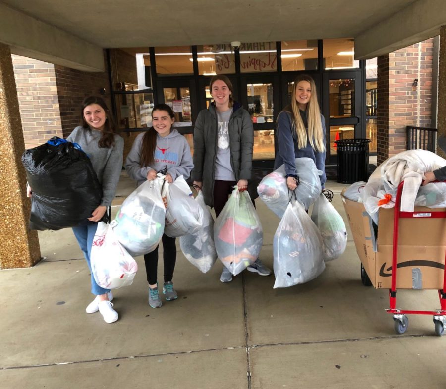 Juniors+Lily+Stiegemeyer+and+Emma+Caplinger+and+seniors+Olivia+Riemer+and+Hayden+Sampson%2C++are+carrying+bags+to+the+truck+to+load+donations+for+St.+Clair+high+school.+Bags+are+being+carried+down+and+loaded+onto+a+truck++to+be+taken+to+kids+in+need.+%E2%80%9CIn+the+morning+at+7am%2C+we+carried++the+bags+down+to+the+main+floor%2C+and+they+were+all+heavy.+Klevens+asked+some+of+the+guys+that+were+sitting+in+the+Art+Foyer++to+help+us+carry+down+the+bags+do+it+went+a+lot+faster.%E2%80%9DYearbook+Editor+-in-Chief%2C+senior+Olivia+Riemer+said.