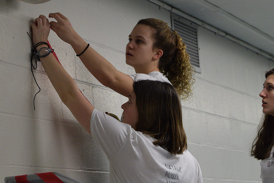 """Setting up streamers in the pool stand for the night, juniors Lydia Roseman and Claire Lynn tape them to the wall. This has been a long standing tradition. """"It was a really exciting night for me because as a junior we were the ones putting the night together so it was cool to see it all fall into place,"""" Lynn said."""