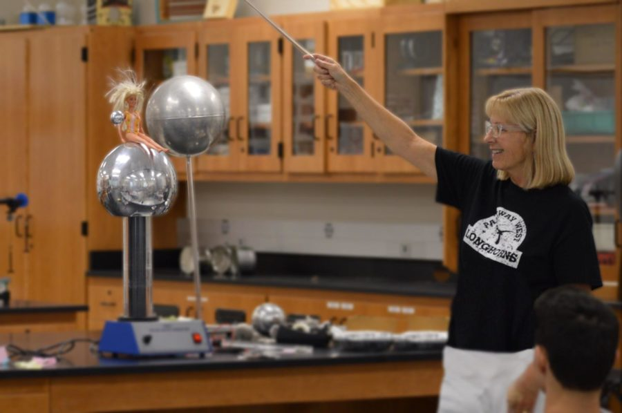 Revolving+a+metal+sphere+around+a+Barbie+doll%2C+physics+teacher+Ellen+Wilke+explains+the+mechanics+behind+electricity.+However%2C+as+much+as+Wilke+enjoys+explaining+electricity%2C+she+would+much+rather+explore+optics.+%E2%80%9CI+really+like+%5Boptics%5D%2C%E2%80%9D+Wilke+said.+%E2%80%9CWave+optics+are+a+really+cool+thing+and+allows+you+to+work+with+material+science%2C+which+is+what+my+undergrad+was%2C+to+work+with+the+crystalline+structure+of+substances.+There%E2%80%99s+so+many+cool+applications+of+optics.+The+basics+will+start+with+mirrors+and+lenses.+Then%2C+it%E2%80%99s+all+about+light+and+the+reflection+of+light%2C+and+the+different+applications+with+lights+and+lasers.%E2%80%9D