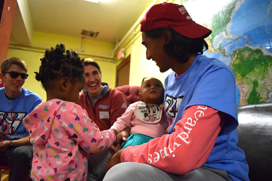 "Senior Farhan Hassan entertains children while volunteering at the Gateway 180 shelter for day of service. Last year students got to read books, played with the kids and sorted out the donation closet. ""Volunteering at Gateway 180 allowed students to not only see the other side of St. Louis, but also it helped those impoverished families to the best of our ability,"" Hassan said. ""Even if it was only one day out of the year, I'm sure we made a huge impact on some of the people staying there."""
