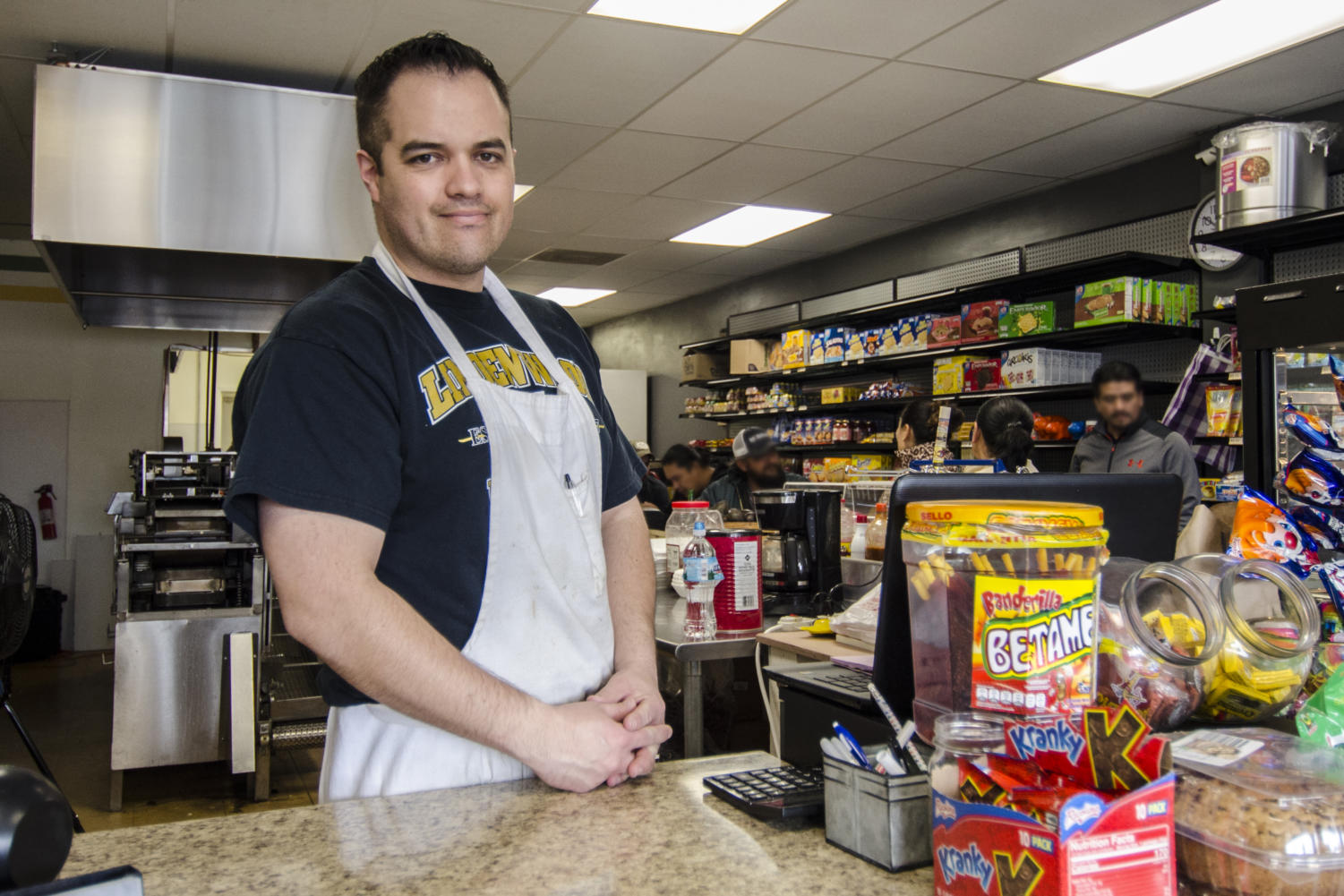 Officer Zeus Hernandez stands at the counter of his restaurant La Tiendita, located at the corner of Clarkson and Manchester. He and his wife own the restaurant, which sells authentic Mexican cuisine along with groceries.