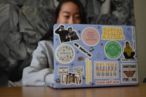 "During second lunch, junior Angie Jia works on homework. As the daughter of immigrants, Jia cares for issues surrounding civil liberties and social causes and chose laptop stickers that would represent her passions. ""My 'Immigrants Make America Great' represents my parents, who I am and who I feel should be empowered in America: immigrants. I value protecting and preserving our environment over industry so I have an environmental awareness sticker too,"" Jia said. ""My 'Believe Women' sticker I got around the time of the Brett Kavanaugh hearings because I strongly agreed with what Dr. Christine Blasely Ford was doing by empowering women and believing their stories."""