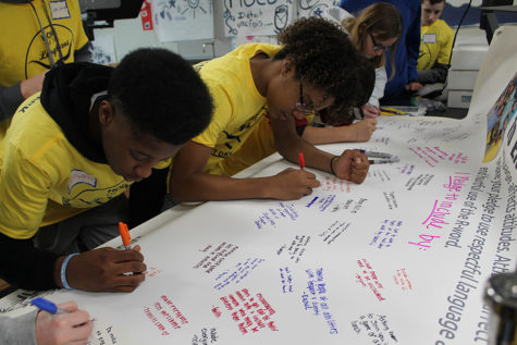 "Writing messages about how to include everyone, freshmen Tre Bell and Ethan McLeod write a note about what they will do to inspire change in the community.  ""I never really thought about everything that happens around me. I really have just been worried about myself, but I realized other people go through a harder time then I do. Now I am going to try help around and be a better person in the community,"" Bell said"