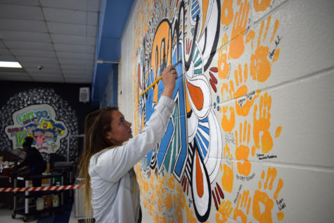 "Adding the final touches to the senior mural, senior Bailey Goughenour finishes painting the second design that her and senior Natalie Butler created. After the first design fell through, the artists came together to come up with the 'Dream Big' design. ""It was just a lot of stress, and it was just really disappointing because we had been cleared. For him to come back and say it's not anymore was just really sad and hurtful,"" Goughenour said. ""But after we were turned down, me and Natalie got together, and we were like, 'what can we do to make this be good?' We just started brainstorming, and we came up with a new design."""