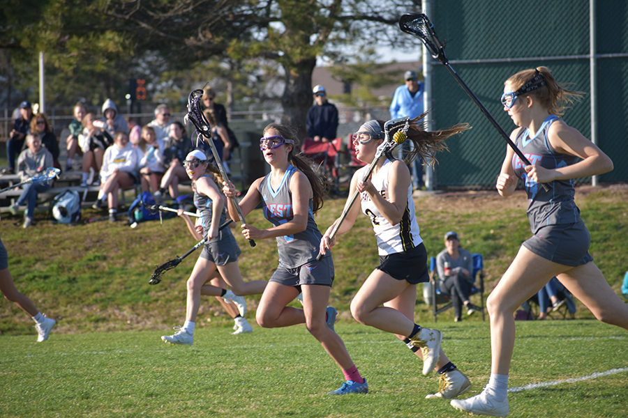 "Stick in the air, junior Charlotte Zera follows the ball in a varsity game against Lafayette April 2. Zera first started playing lacrosse when a tennis teammate encouraged her to try out for the team. ""The kind of culture I hope to inspire in the lacrosse program is one where everyone can freely make friends and help each other grow not only in lacrosse, but in their character, sportsmanship and athleticism,"" Zera said."