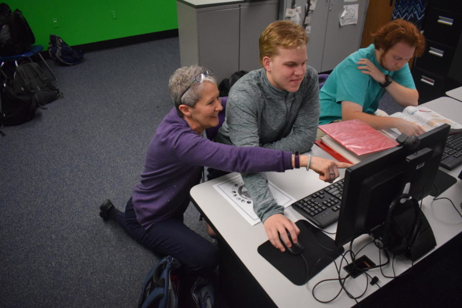 "Business teacher Laura Glenn helps junior Walker Piles with an assignment in class. Throughout her time of teaching, Glenn has taught Accounting, Web Design and Intro to Computer Science and Technology. ""The thing I'll miss the most is working with students and sharing knowledge with them,"" Glenn said. ""[It's] really exciting to see how just a little bit of what I might've introduced them to here has turned into a career for them and something that they are excited about."""