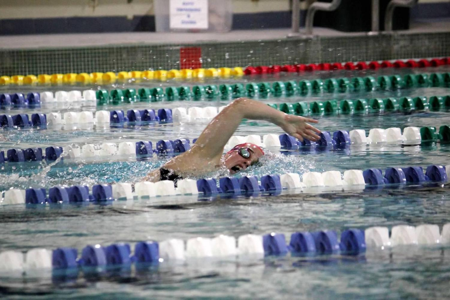 "Senior Maria Newton swims during her practice competition at Marquette Relays during the start of her season. The swim meet is a long standing tradition for St. Louis area high school teams to participate in low-stake competitions. ""It was always one of my favorite swim meets because I love to be reminded that the sport is about racing, and that is what we need to be focused on,"" Newton said. ""You just need to be faster than the person next to you."""