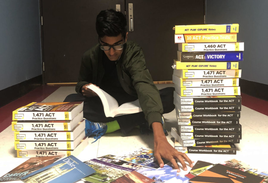 "Between stacks of ACT prep books, junior Ronik Bhaskar reaches forward for college pamphlets as he looks towards higher education. Bhaskar earned a 36 on his ACT. ""Getting a 36 was a combination of lots of early mornings doing practice tests and a healthy dose of luck,"" Bhaskar said."