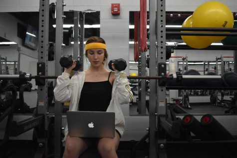 Junior Caroline Judd attempts to follow an online weightlifting video. In the summer of 2020 Parkway is introducing a new online physical education course available to all students.