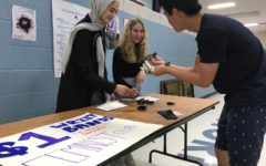"""Selling an """"I STAND WITH REFUGEES"""" wrist band to junior Jon Ma during second lunch, junior Sabrina Bohn and sophomore Ulaa Kuziez raise awareness for the Immigrant and Refugee Women's Program. The feminist club voted earlier in the year to provide money to that group in order to expand their impact on the global community. """"Last semester we had a group vote between three different charities. We had one that was a women's shelter that helped women who experienced domestic abuse, the Immigrant and Refugee Women's program and another women's shelter with a different focus. The group members voted and decided on the Immigrant and Refugee program to bring awareness, not just in our community and school, but to a bigger world,"""" Bohn said. Photo by Kathryn McAuliffe"""