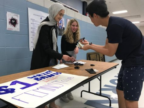 "Selling an ""I STAND WITH REFUGEES"" wrist band to junior Jon Ma during second lunch, junior Sabrina Bohn and sophomore Ulaa Kuziez raise awareness for the Immigrant and Refugee Women's Program. The feminist club voted earlier in the year to provide money to that group in order to expand their impact on the global community. ""Last semester we had a group vote between three different charities. We had one that was a women's shelter that helped women who experienced domestic abuse, the Immigrant and Refugee Women's program and another women's shelter with a different focus. The group members voted and decided on the Immigrant and Refugee program to bring awareness, not just in our community and school, but to a bigger world,"" Bohn said. Photo by Kathryn McAuliffe"
