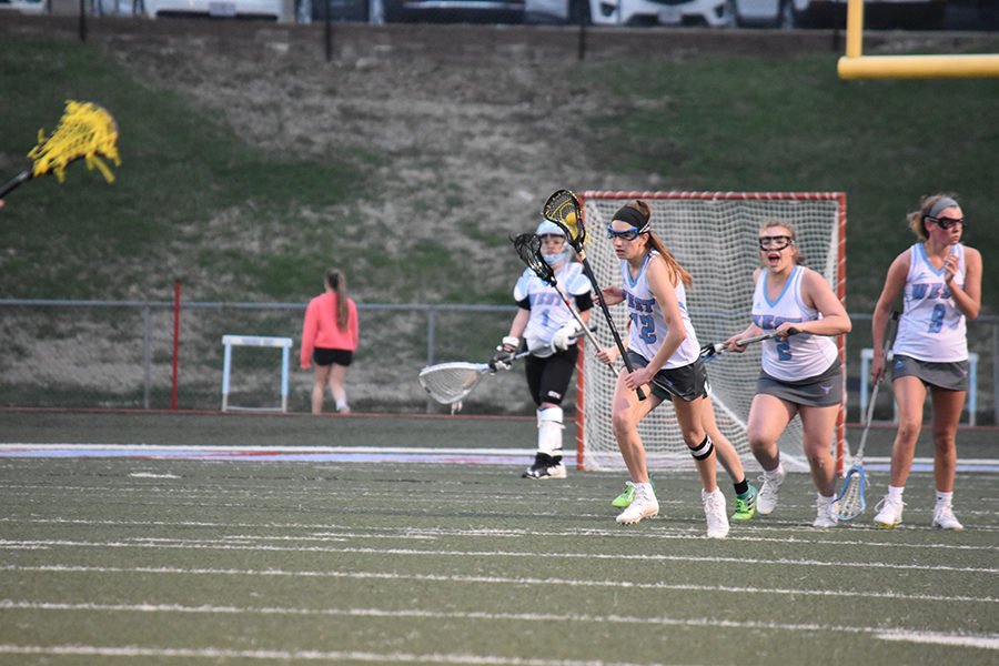 Looking+for+an+open+teammate%2C+junior+Jenna+Mercer+travels+down+the+field+in+a+game+against+Pattonville.+The+game+went+into+overtime+with+a+score+of+6-6+until+Mercer+scored+the+game+winning+goal.+%E2%80%9CI+was+so+excited+and+surprised+because+I+didn%27t+think+It+was+going+to+make+it%2C+but+then+I+saw+it+did+and+hearing+everyone+cheer+was+so+exciting%2C%E2%80%9D+Mercer+said.
