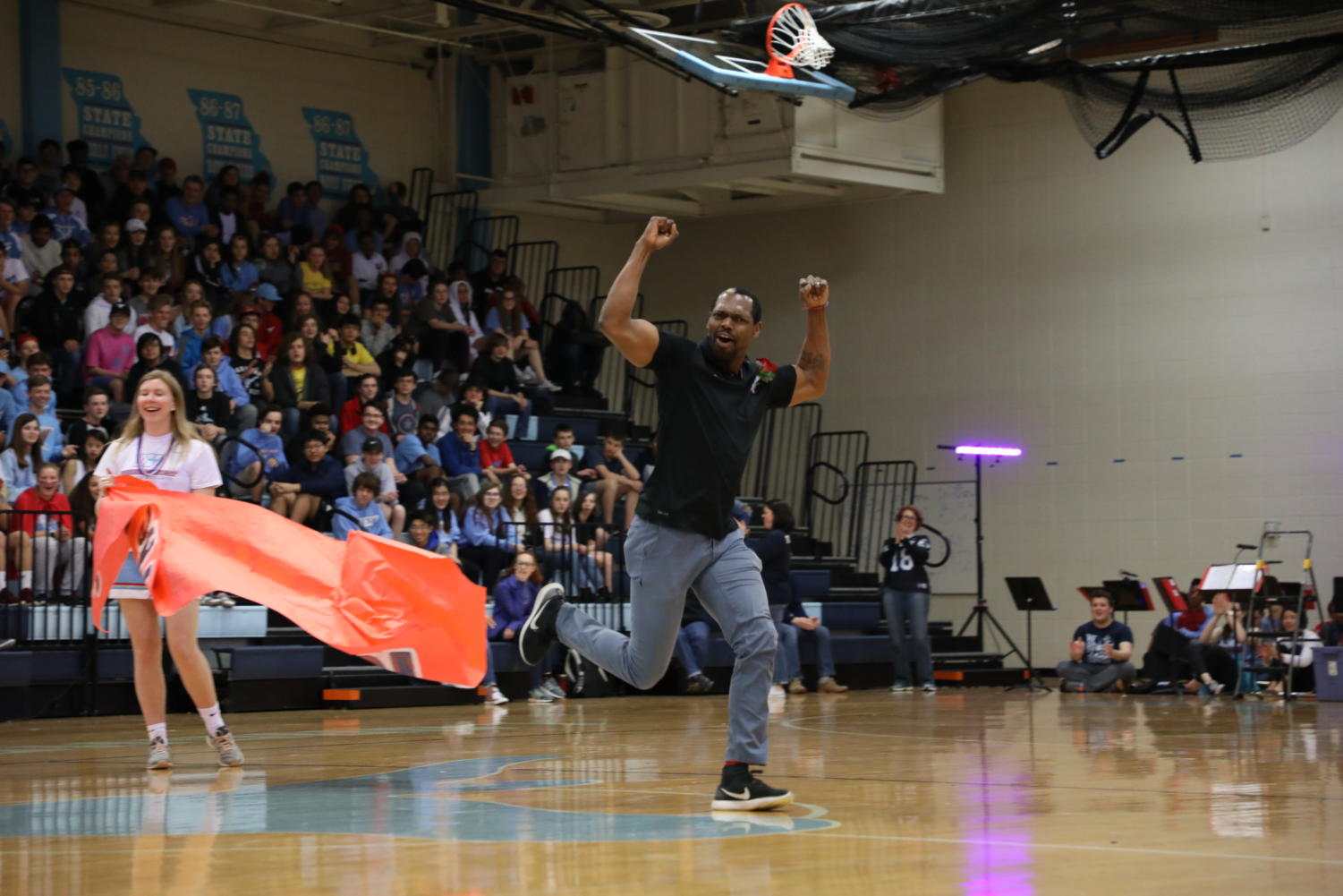 """Beginning his victory lap around the gym, 2019 Teacher of the Year awardee Emanuel Young pumps his fists to energize the crowd at the Spring Pep Rally, March 29. This is Young's fourth year teaching business at West High.. """"I was in a state of disbelief,"""" Young said. """"My heart was racing; it was one of those things you felt like you should have known but didn't."""""""