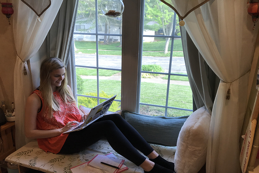 "Perched in her window seat with her laptop, junior Kelsey Long works on her novel. Long has been working on revising and editing since August 2018. ""I make the most progress during the summers. I usually write from 4-9 p.m. and then sporadic times throughout the day if I'm at home. During the school year, I work a couple hours in the evening a couple times a week and then some on the weekends,"" Long said."