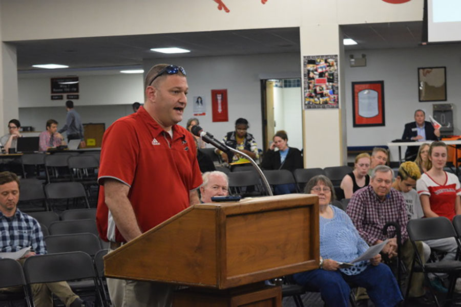 Ken Susman stands in front of the board of education in the foyer of Central Middle school. He is wearing a red shirt and speaking into the microphone at the podium, empassioned.