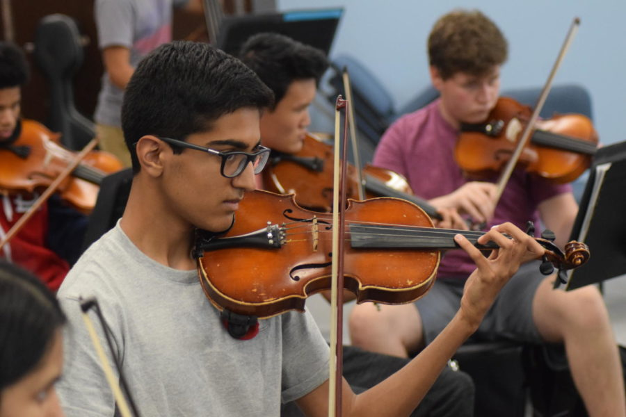 """Directed by Ed Sandheinrich (not pictured), juniors Ronik Bhaskar, Dennis McMorrow and Daniel Yu play their instruments in Symphonic Orchestra. All levels of orchestra participate in the reflection by playing songs that they are able too that the seniors choose. """"It's different every day, a new adventure every day, and it keeps things fresh,"""" Sandheinrich said."""