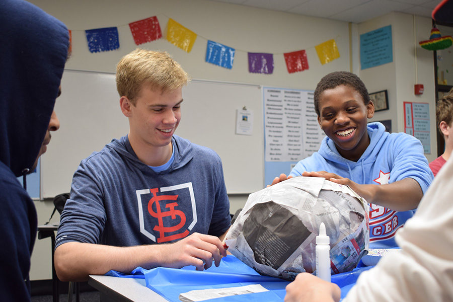 "Using balloons and newspaper to construct piñatas in Eileen Rodriguez-Kiser's Spanish II class, sophomore Logan Wich and junior Ridwan Oyebamiji laugh as they glue together their project. The class has been exploring different types of birthday celebrations in Hispanic countries. ""It was really cool to take a hands-on approach to learning Spanish,"" Oyebamiji said. ""Instead of just sitting at a desk, we were able to be immersed in the culture, which really deepens your understanding."""