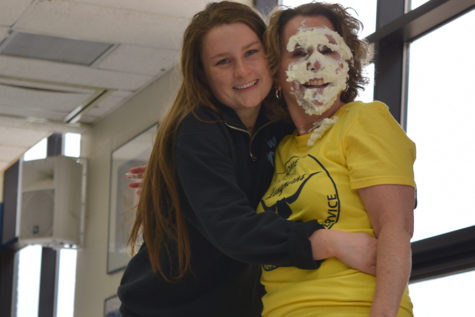 "Covered in whipped cream, Spanish teacher Eileen Kiser hugs sophomore Zoe DeYoung in the cafeteria. Kiser braced for impact before DeYoung pied her to raise money for Friends of Kids with Cancer. ""Mrs. Kiser and I have a really close relationship, and we were both really hoping that my name would be drawn so I could pie her. When my name was drawn, we immediately looked for each other, and we were so surprised,"" DeYoung said."