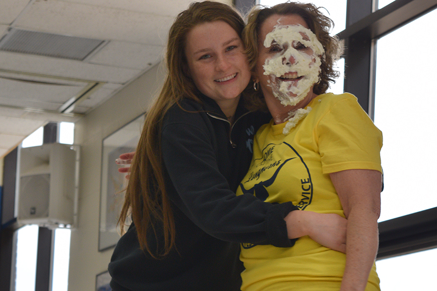 """Covered in whipped cream, Spanish teacher Eileen Kiser hugs sophomore Zoe DeYoung in the cafeteria. Kiser braced for impact before DeYoung pied her to raise money for Friends of Kids with Cancer. """"Mrs. Kiser and I have a really close relationship, and we were both really hoping that my name would be drawn so I could pie her. When my name was drawn, we immediately looked for each other, and we were so surprised,"""" DeYoung said."""