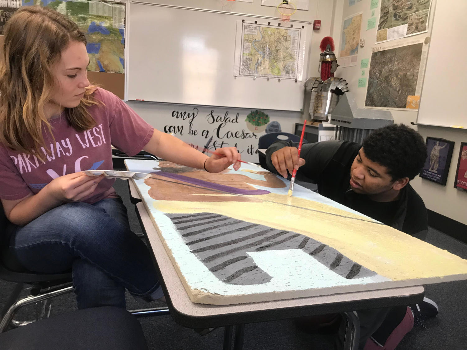 Finishing a tile for Latin teacher Tom Herpel's room, sophomores Emma Smout and Myles Mosley paint. This tile took a year to make and is being finished with the collaborative effort of Smout, Mosley, and sophomore Reese Berry.