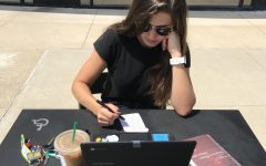 Senior Emma Caplinger studies a to-do list of summer assignments at the Town and Country Crossing Starbucks. Students have the entire summer to complete their homework, although most wait until the end of summer break.