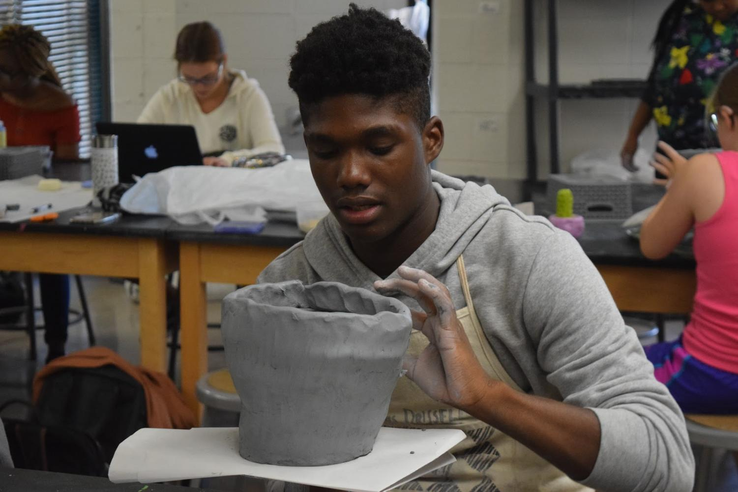 """Molding the clay, junior Ledaniel Jackson works on building the base of his ceramic cactus. After the class completed their donuts project, they began creating cactuses for the coil building unit. """"I think the best part about the class is having the freedom to create [ceramics] on our own,"""" Jackson said. """"It makes the class really fun."""""""