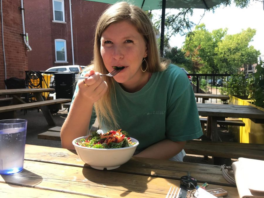 Enjoying+the+sun+on+the+outdoor+patio+at+Lulu%E2%80%99s+Local+Eatery%2C+senior+Quinn+Berry+enjoys+a+vegan+kale+salad.+%0A