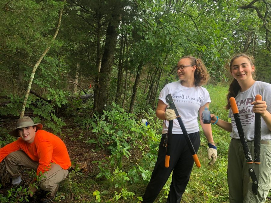 "Sophomore Maura Collins and junior Ella Seigel hold gardening shears after cutting out invasive species of honeysuckle and privet. After, they sprayed the area with herbicide to ensure it did not return. ""It felt really rewarding to meet a bunch of like-minded individuals working together to see real change in the environment that we restored,"" Seigel said."