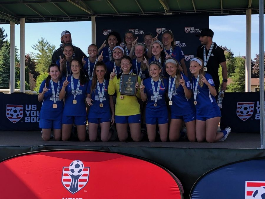 """Posing with her team on the champions stage, sophomore Ella Roesch holds one finger up, indicating that her Lou Fusz Blue team won first place in the US Youth Soccer Midwest Regional Championships June 26 in Saginaw, Mich. Roesch's team beat out teams from 15 other states, all located in the Midwest, beating Iowa Rush 3-1 in the finals. """"The first goal of the game was my favorite part because I got the assist. The one who scored was one of my good friends on the team and ran right to me. We practice our celebrations, so we showed off to our parents. It was a lot of fun, but after celebrating, it was back to game time,"""" Roesch said."""