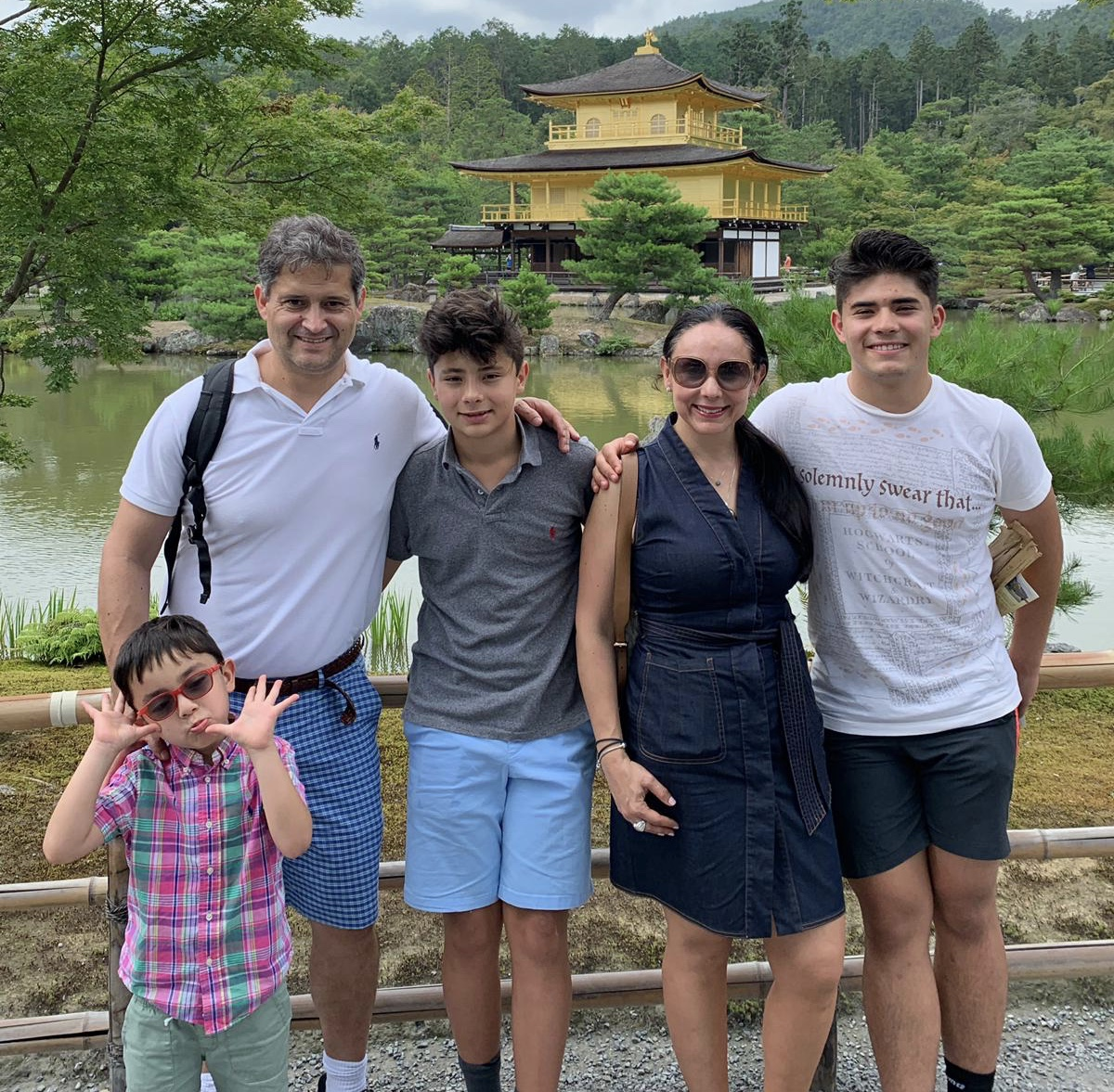 "Visiting the Kinkaku-ji, a Zen Buddhist temple, sophomore Santi Lugo and his family pose for a photo. The temple, also known in translated Japanese as the ""Temple of the Gold Pavilion,"" is one of Japan's most popular buildings. ""It was a long trail, trees all around, and the sound of rocks being stepped on crowded my ears. When you're walking, you're unable to see anything until suddenly you see a gold point rising above the trees that leads to the peaceful stream below the astonishing temple,"" Lugo said"