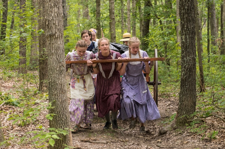 "Pulling a handcart through the woods, sophomore Izzie Finlinson (middle) takes part in the women's pull part of the journey. Many of the pioneers taking the trek lost or had to leave their husbands along the way, so they were the ones who had to pull the carts along the end of the trail. ""This pull was a really emotional time for all of us because we were able to put ourselves in those women's shoes during a time where they really struggled,"" Finlinson said."
