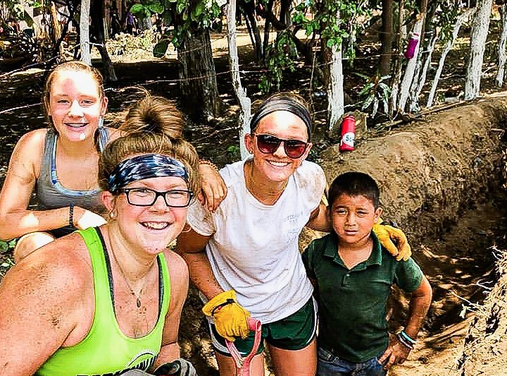 """Coated in dirt, junior Reese Berry poses with people in her mission group, Amigos for Christ, and with a child from the village of Espavel. This was Berry's first mission trip, but she wants to do more in the future. """"I think one of the things that really made my heart melt was when one of the Nicaraguans said to us, 'you dig as though the water will be yours',"""" Berry said."""
