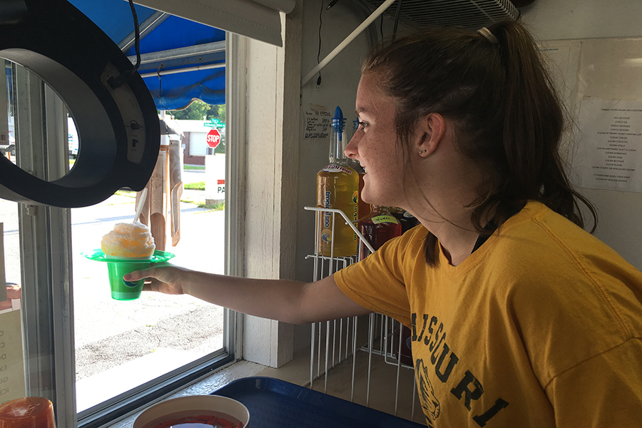"Handing a snow cone to a customer, employee and junior Audrey DeYoung fulfills her childhood dream of working at Tropical Sno Manchester, where she makes minimum wage. To reach a teenage demographic, DeYoung and her coworker created the Instagram account @trosnomanchester in hopes of having more teenagers drop by as customers. ""What drew me to it was that it's such a little shack and kind of a unique job to have,"" DeYoung said. ""Everyone I know goes there pretty often, so I knew I'd be able to see a lot of people from school. It annoys me when my friends are getting snow cones together, and I can't be with them because I'm working."""