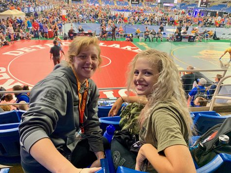 "Watching teammates wrestle from the bleachers, sophomore Paige Wehrmeister and teammate Emma Cole bond through their common interests. Following the trip to Fargo, Wehrmeister continued to spend time with the friends she made during her trip to Fargo. ""We were all representing the same state, and after all that time together, I developed close friendships with some of the girls,"" Wehrmeister said."