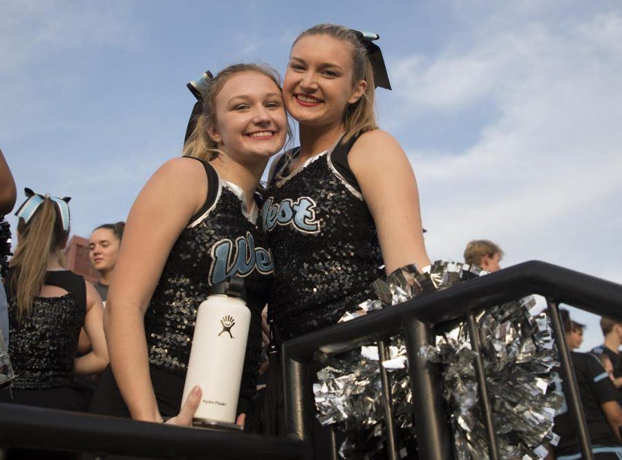 """Fresh off their first performance at Red and Blue Night, freshman Kelsea Wilson hugs her sister, senior Kristin Wilson, excited that they completed their first routine together. Both tried out for poms and were excited to make varsity, it being the only year they will both be on the team. """"My favorite part is the games, getting ready with her beforehand and having our parents get to watch us both perform,"""" Kristin said."""