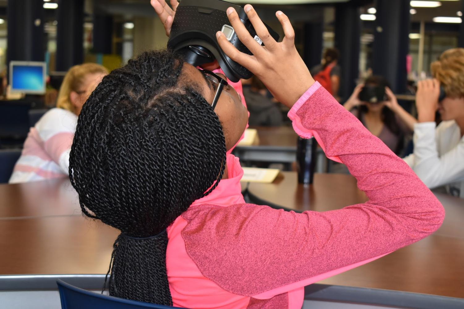 "Looking into a virtual reality headset, sophomore Dyani May takes a virtual tour of the United States Holocaust Memorial Museum in her English II class Sept. 17. This was English teacher Casey Holland's first time using VR in his classroom and was pleased with his students' reaction to the tour. ""It was different and exciting and fun,"" Holland said. ""The kids thought it was neat. When we started off, they were taking pictures of each other with their phones, but as the material we were talking about got more in depth, you could hear them saying 'Oh wow,' and hear them having some really good conversations with one another."""