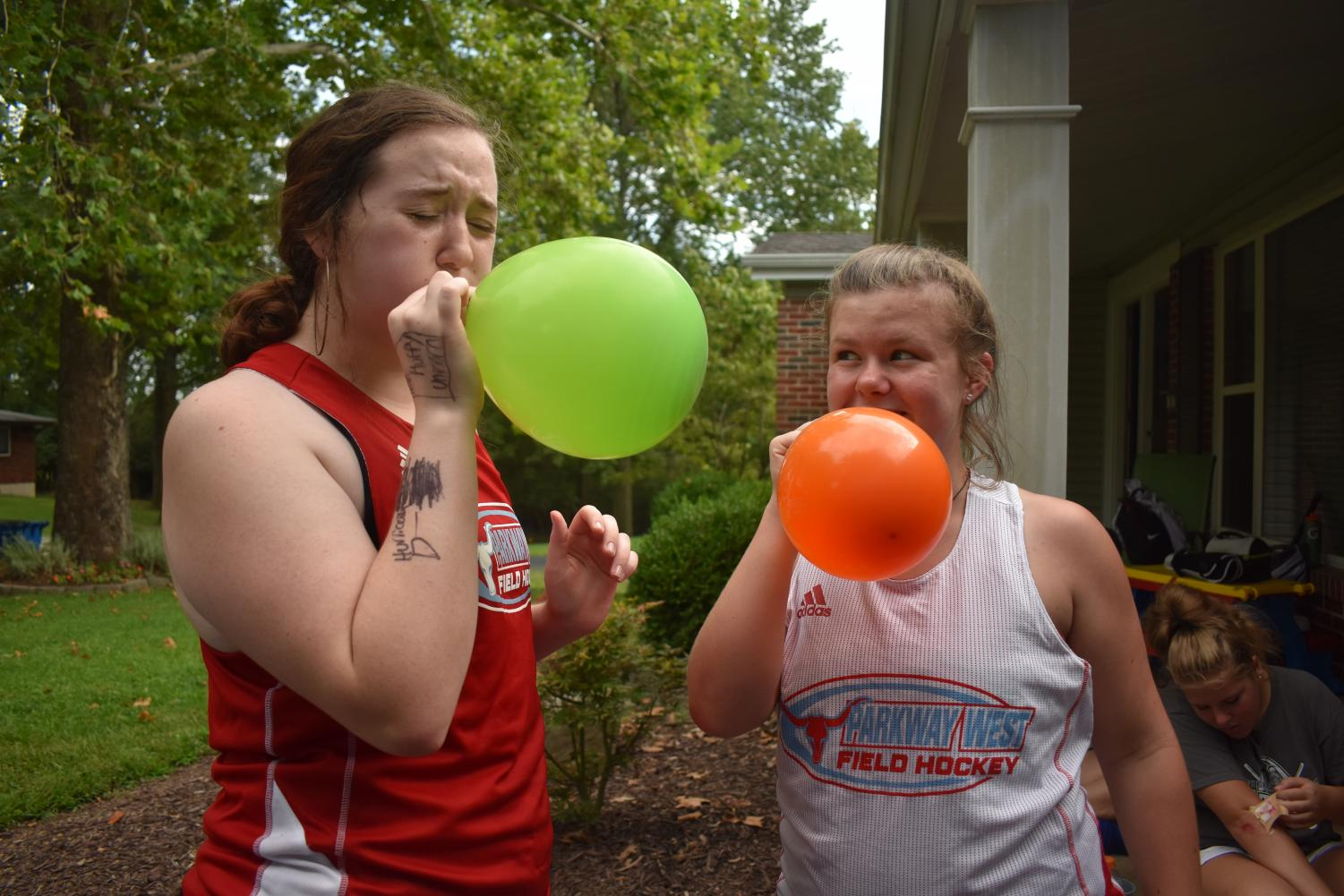 """At a field hockey team dinner, sophomores Sarah Kline and Annie Zahoran blow up another balloon for a competition to see who could not let the balloon drop to the floor on Sept. 2. Members of the field hockey program met at Coach Dawn Callahan's house for a team dinner of Italian food. """"We were playing keep it up with the balloons as a competition between our three teams, but we ended up popping all of them. I was really struggling [to blow the balloons up] but we ended up having a lot of fun anyways."""""""