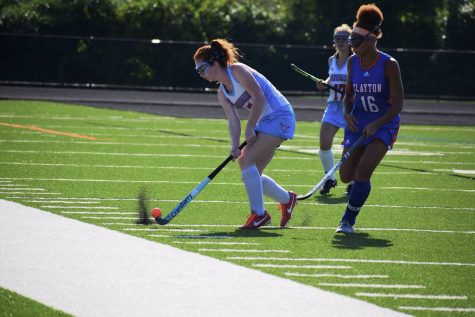 Making a pass down the field, senior and varsity midfielder Carly Anderson strikes the ball past a Clayton defender. Anderson has played varsity all four years of high school.