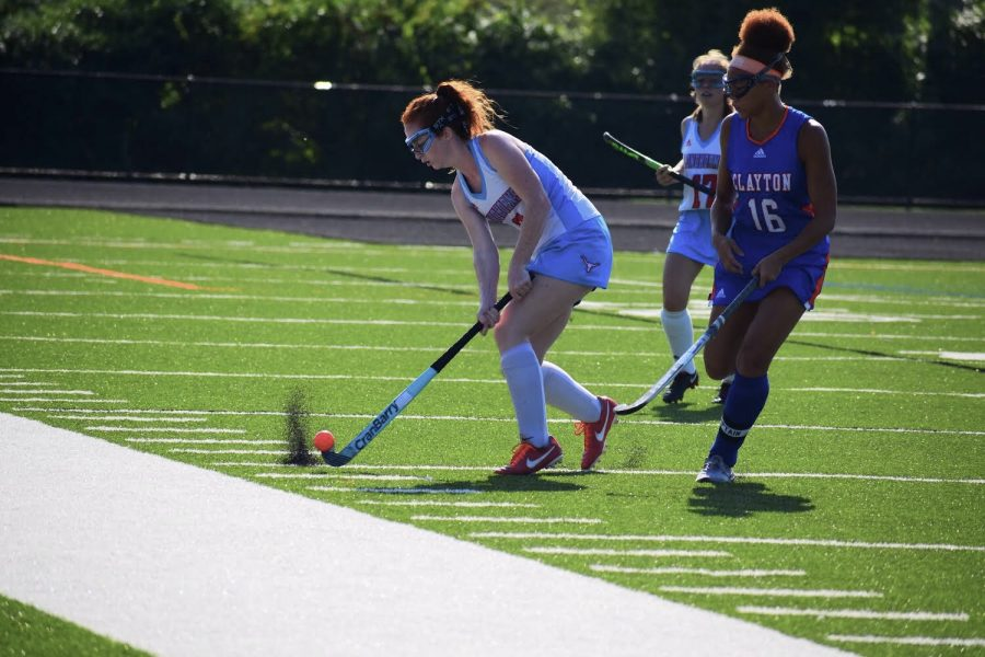 Making+a+pass+down+the+field%2C+senior+and+varsity+midfielder+Carly+Anderson+strikes+the+ball+past+a+Clayton+defender.+Anderson+has+played+varsity+all+four+years+of+high+school.+%22I+am+really+excited+about+this+season%2C%22+Anderson+said.+%22We+started+out+a+lot+stronger+than+usual+and+we%27re+determined+to+finish+out+the+season+that+same+way.%22