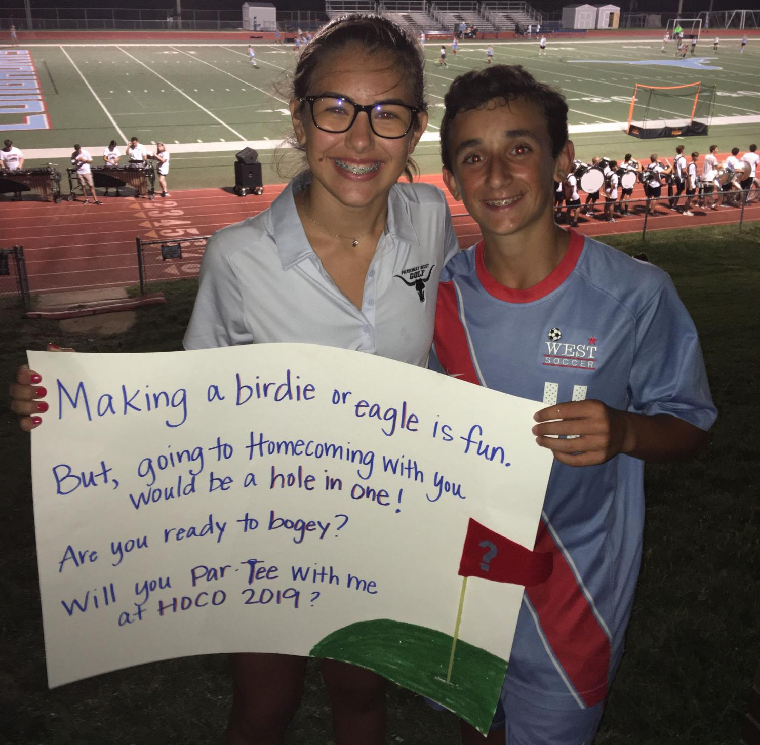 After+participating+in+a+soccer+scrimmage%2C+freshman+Adam+Lancia+gives+his+golf-inspired+homecoming+sign+to+freshman+Gabi+Badami.+Lancia+surprised+her+with+his+sign+at+Red+and+Blue+night+Aug.+24.+Badami+was+expecting+to+get+asked+by+Lancia+after+her+golf+match+but+that+did+not+happen..+%E2%80%9CI+was+really+happy+and+surprised+when+he+asked+in+front+of+everyone%2C%E2%80%9D+Badami+said.+%E2%80%9CI+don%E2%80%99t+think+I+stopped+smiling+until+I+went+to+sleep+that+night%E2%80%93I%27m+really+looking+forward+to+spending+homecoming+with+him.%E2%80%9D%0A
