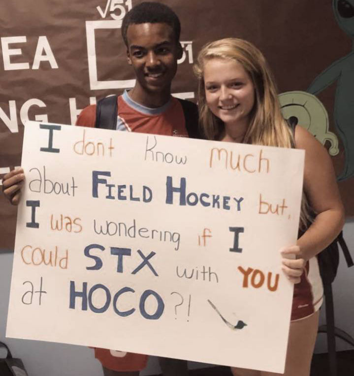 Freshman+Christian+Flemming+proposes+to+freshman+Molly+Glisson+in+the+math+hallway+before+class.+Glisson+was+excited+about+how+Flemings%27+field+hockey+themed+sign+turned+out.+%E2%80%9CI+didn%E2%80%99t+think+I+was+going+to+get+asked%2C%E2%80%9D+Glisson+said.+%E2%80%9CSo+when+I+saw+his+sign%2C+I+was+really+surprised+and+happy+because+I+had+a+date%2C+and+it+was+really+cute+and+well+put+together.%E2%80%9D