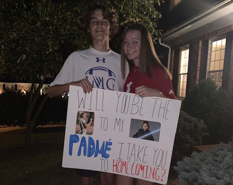 Posing+outside+her+house%2C+freshman+Derrien+Gatchel+asks+freshman+Makinsey+Drake+to+Homecoming.+Gatchel+and+Drake+are+both+fans+of+the+Star+Wars+franchise.+%E2%80%9CI+looked+on+Pinterest+for+Star+Wars+homecoming+signs+and+saw+a+similar+idea+to+mine%2C%E2%80%9D+Gatchel+said.+%E2%80%9CIt+didn%27t+take+too+long+to+make%2C+and+I+just+made+it+in+my+living+room.%E2%80%9D%0A