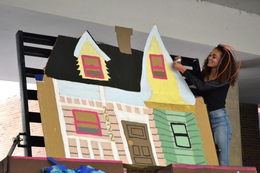 """Hannah Lumpkins makes finishing touches for a house that will be on her float, corresponding with her grade's """"Up"""" theme."""