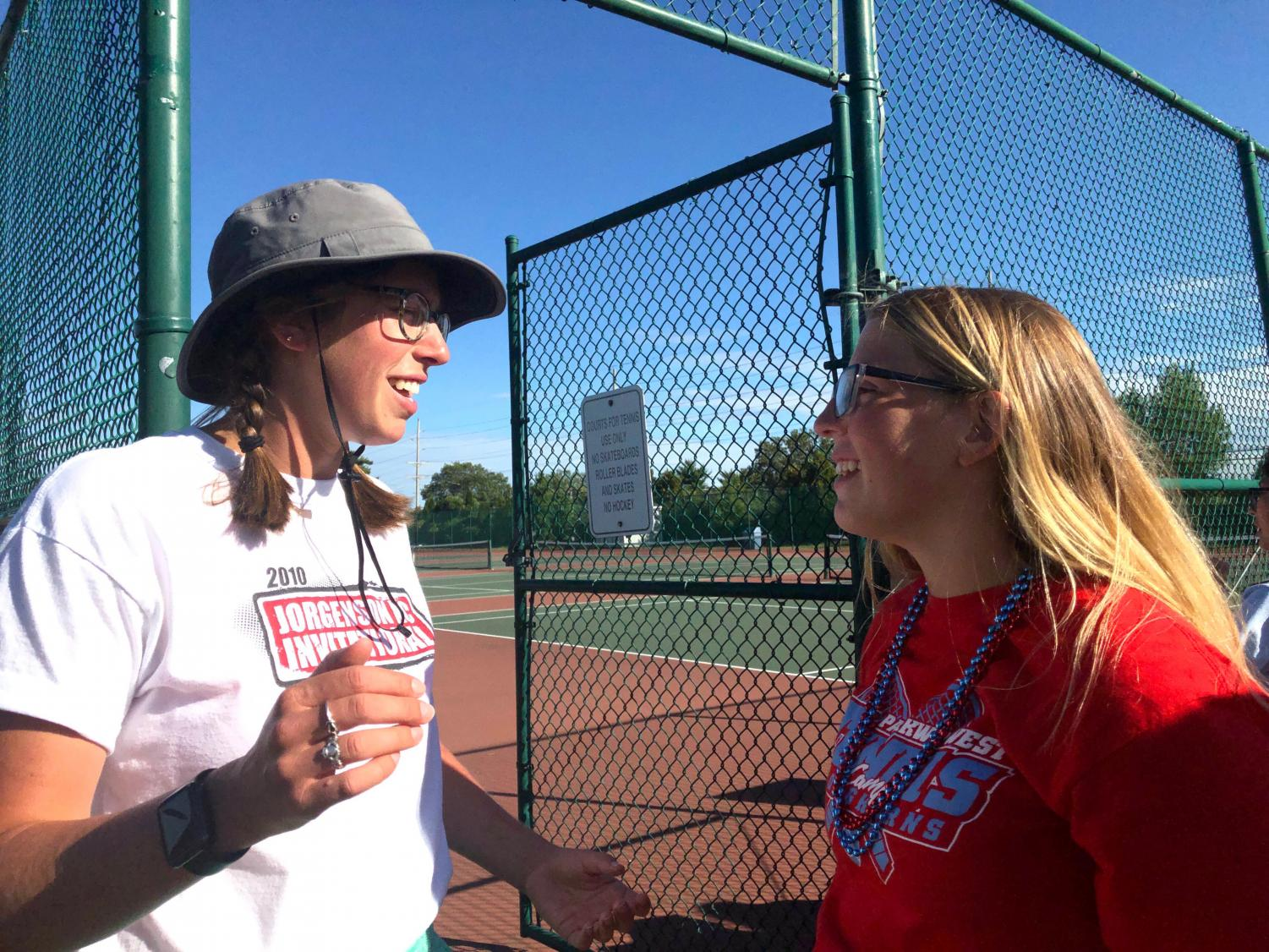 "JV tennis coach Audra Hartwell gives sophomore Betsy Weaver parade line up details before the Homecoming parade begins. Hartwell made a point to her players about having fun while also competing at a high level. "" I want tennis to be the best part of their day because it keeps them coming back,"" Hartwell said. ""I want them excited to come to practice or a match."""