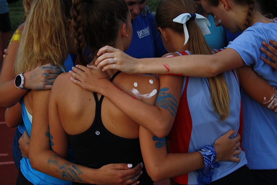 The girls cross country team gathers in a huddle during Red and Blue Night.