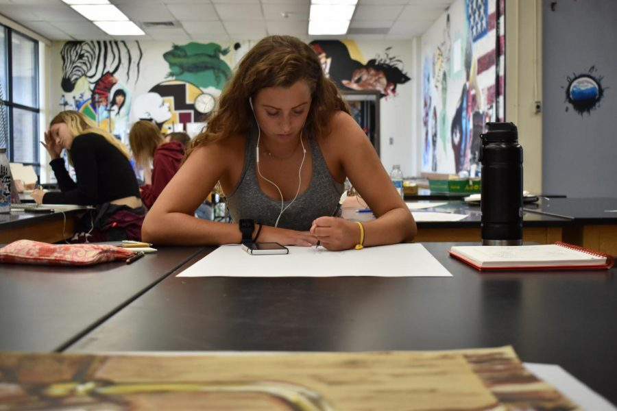 Junior Anna Butler listens to music as she works on a piece in her AP studio art class.